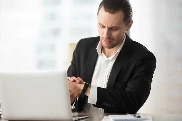 Homem de negócios que olha o relógio de pulso na mesa do trabalho no escritório.