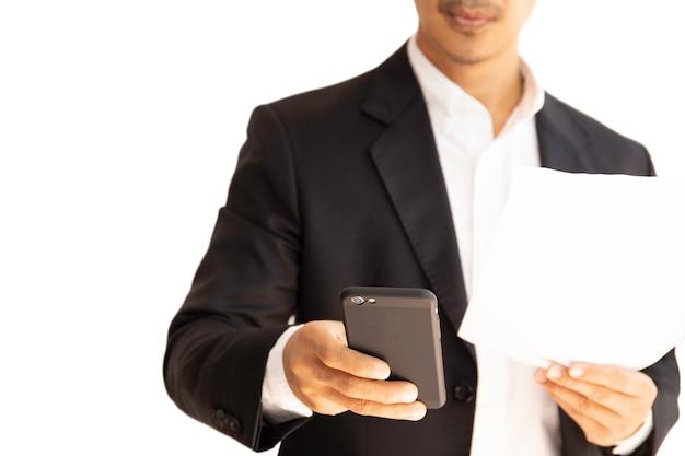 Homem de negócios que olha o telefone celular e que guarda o documento no trajeto de grampeamento.