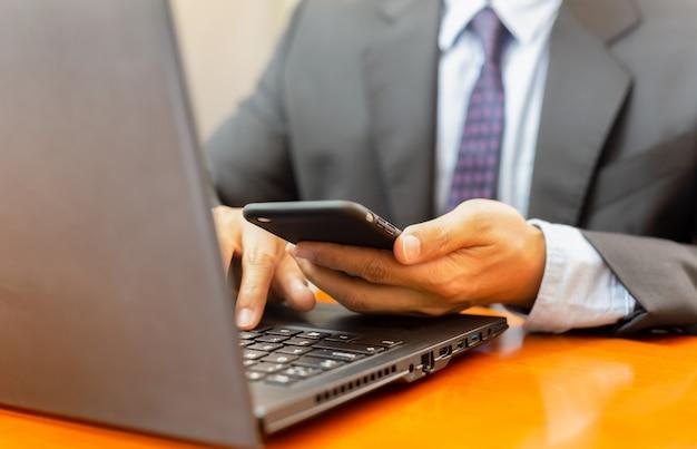 Homem de negócios que olha o telefone celular e trabalho no portátil.