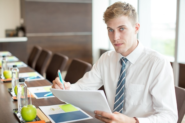 Homem de negócios que prepara a fala na mesa da conferência