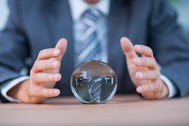 Homem de negócios que prevê uma bola de cristal