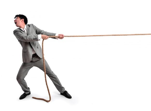 Homem de negócios que puxa em uma corda