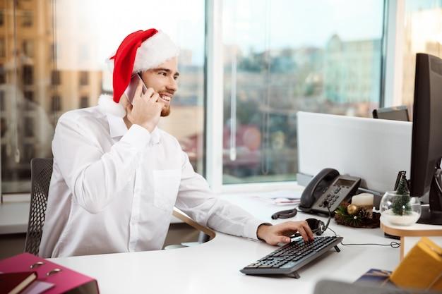 Homem de negócios que sorri falando no telefone no dia de natal do worplace.