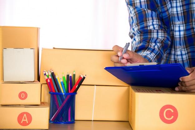 Homem de negócios que trabalha com telefone celular e que embala o escritório marrom da caixa em casa dos pacotes.