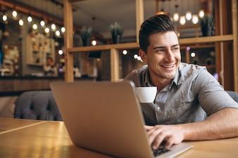 Homem de negócios que trabalha no laptop em um café