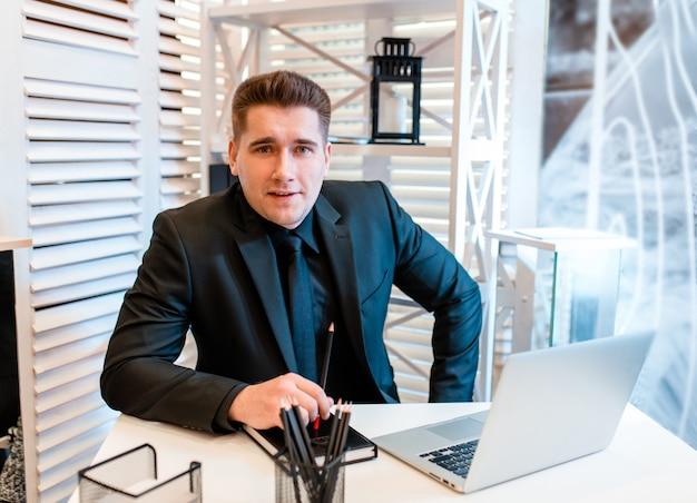 Homem de negócios que trabalha no portátil no escritório bonito e que sorri.