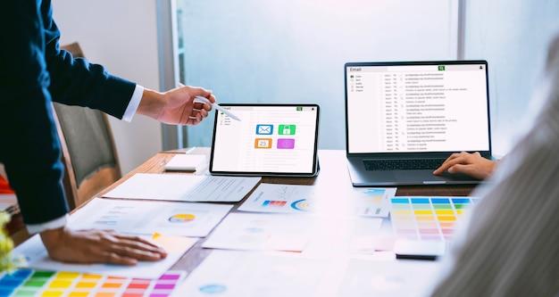 Homem de negócios que usa a comunicação da conexão da tela do email da leitura do portátil e da tabuleta.
