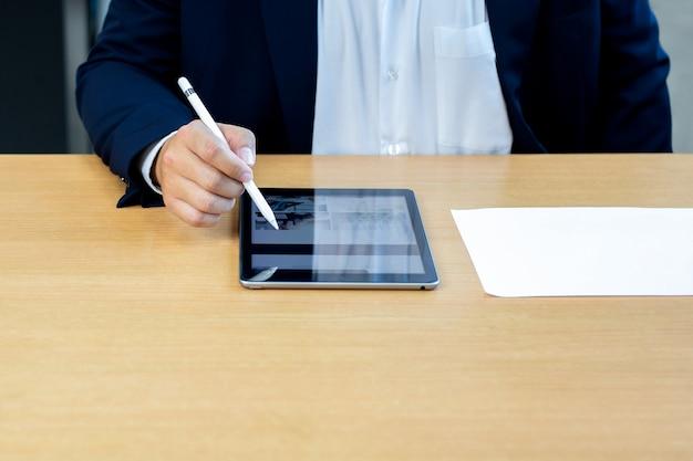 Homem de negócios que usa a pena digital da tabuleta no notped com carta conservada em estoque de papel na mesa.