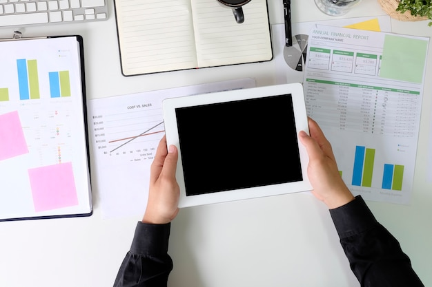 Homem de negócios que usa a tabuleta do modelo na mesa de escritório com relatório do papel da finança e vista superior.