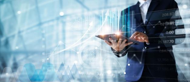 Homem de negócios que usa a tabuleta que analisa dados das vendas e carta do gráfico do crescimento econômico.