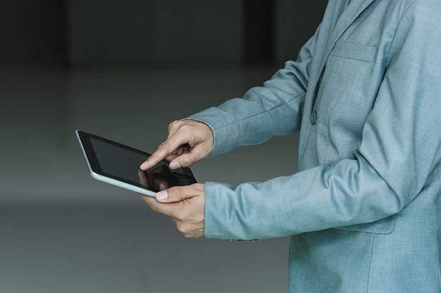 Homem de negócios que usa a tecnologia com tabuleta, conceito do internet da tecnologia do negócio do serviço ao cliente do suporte laboral.