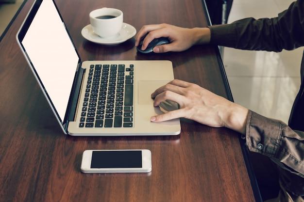 Homem de negócios que usa o computador portátil na mesa no escritório.