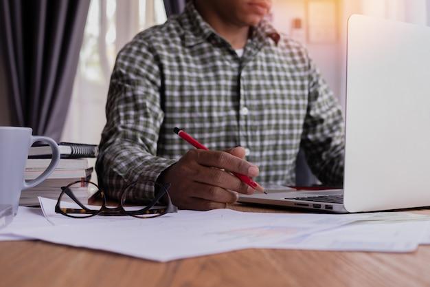 Homem de negócios que usa o portátil e escrevendo no documento no escritório.