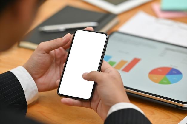 Homem de negócios que usa o smartphone do modelo com tela vazia e dados digitais da finança da análise da tabuleta.