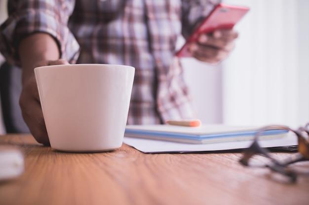 Homem de negócios que usa o smartphone e bebe o café.