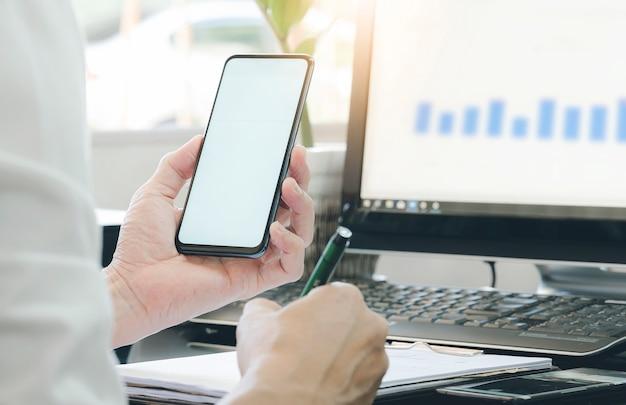 Homem de negócios que usa o smartphone e escrevendo no branco do bloco de notas que trabalha com computador.