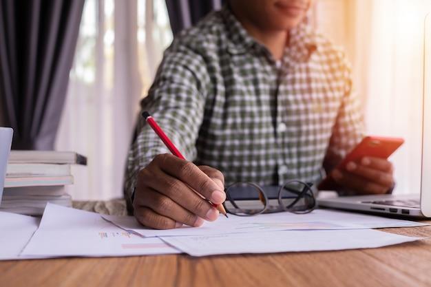Homem de negócios que usa o smartphone e escrevendo no papel.