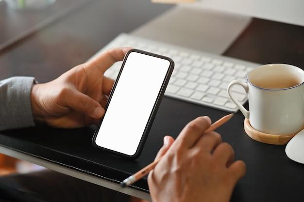 Homem de negócios que usa o telefone celular na mesa, telefone esperto que mostra a tela vazia para a montagem.