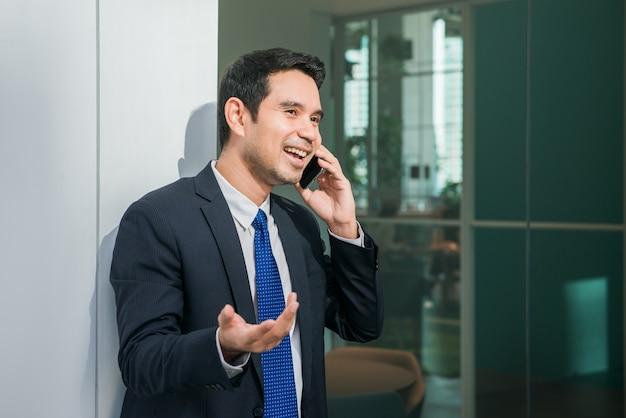 Homem de negócios que usa o telefone móvel que faz mensagens de texto fora do escritório na cidade urbana com edifícios de arranha-céus em segundo plano. jovem homem caucasiano segurando smartphones para o trabalho de negócios.