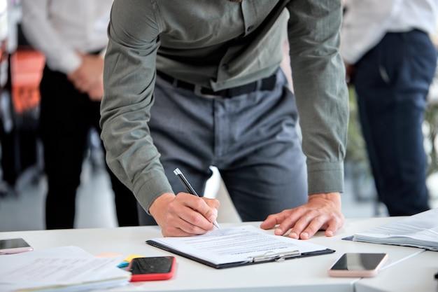 Homem de negócios recortado, assinando contrato financeiro, colocar a assinatura de escrita no formulário de documento de preenchimento de papel corporativo legal, comprar empréstimo de seguro, fazer acordo comercial, fechar as mãos de vista. copie o espaço