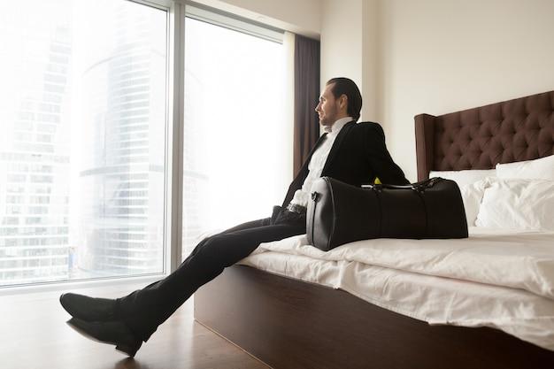 Homem de negócios relaxado que senta-se na cama além do saco da bagagem.