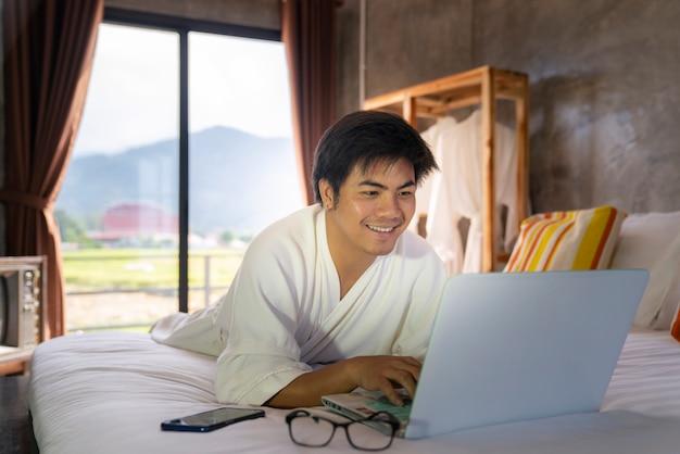 Homem de negócios relaxar e trabalhar pelo computador no quarto da cama