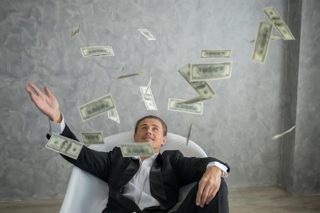 Homem de negócios rico que encontra-se na banheira enchida com as notas de banco do dólar. conceito de negócio de sucesso.