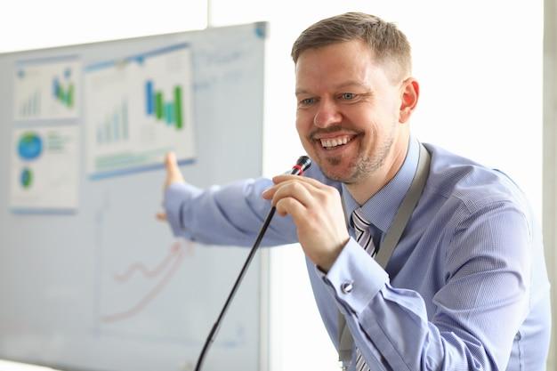 Homem de negócios rindo mostrando gráficos e diagramas