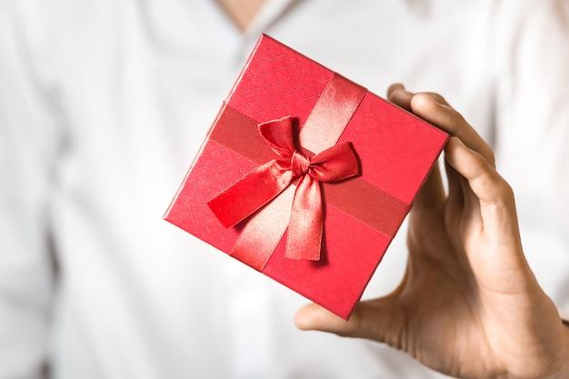 Homem de negócios segura a caixa de presente vermelha nas mãos.