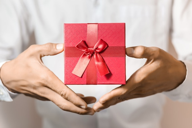 Homem de negócios segura caixa de presente vermelha nas mãos.