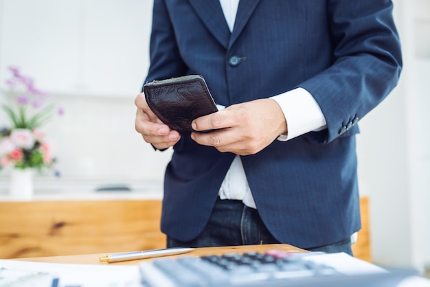 Homem de negócios, segurando a carteira de homens em pé.