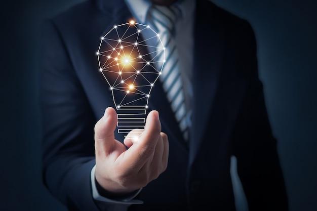 Homem de negócios, segurando a lâmpada de luz na mão