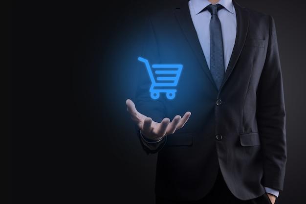 Homem de negócios segurando carrinho de compras carrinho mini em pagamento digital empresarial