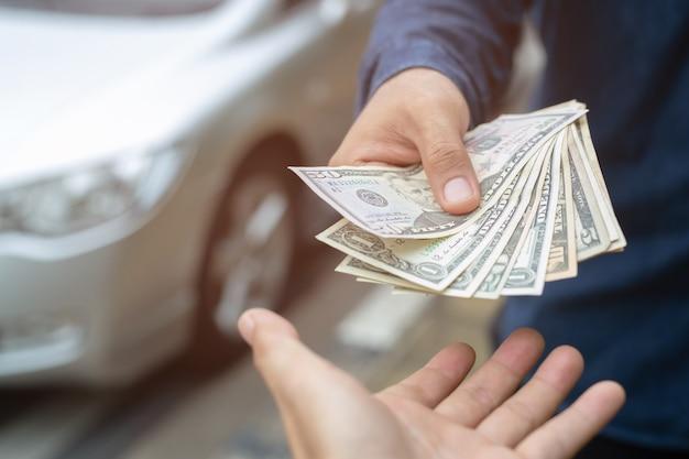 Homem de negócios segurando dinheiro na mão carrinho frente carro preparar pagamento em prestações