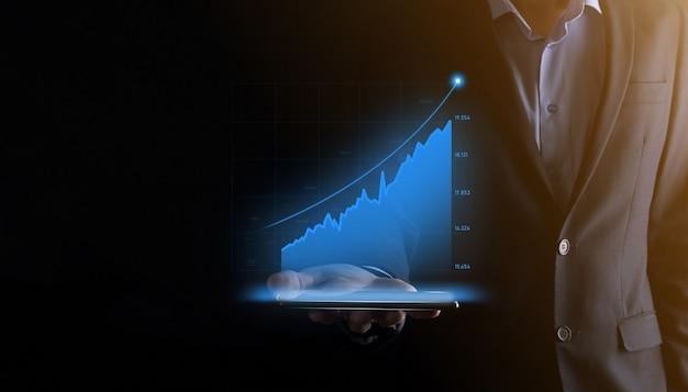 Homem de negócios segurando e mostrando gráficos holográficos e estatísticas do mercado de ações ganham lucros conceito de planejamento de crescimento e estratégia de negócios exibição de boa economia em tela digital