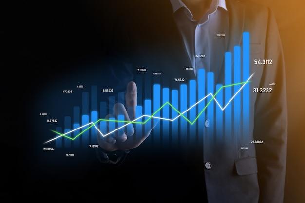 Homem de negócios segurando e mostrando gráficos holográficos e estatísticas do mercado de ações obtém lucros