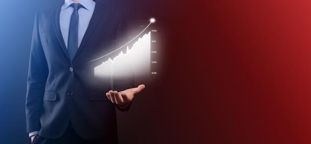 Homem de negócios segurando gráficos holográficos e estatísticas do mercado de ações ganham lucros. conceito de crescimento