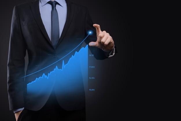 Homem de negócios segurando gráficos holográficos e estatísticas do mercado de ações ganham lucros. conceito de planejamento de crescimento e estratégia de negócios. exibição de tela digital de forma econômica.