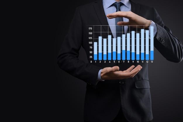 Homem de negócios segurando gráficos holográficos e estatísticas do mercado de ações ganham lucros.