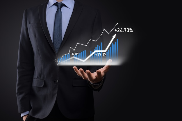 Homem de negócios segurando gráficos holográficos e estatísticas do mercado de ações obtém lucro