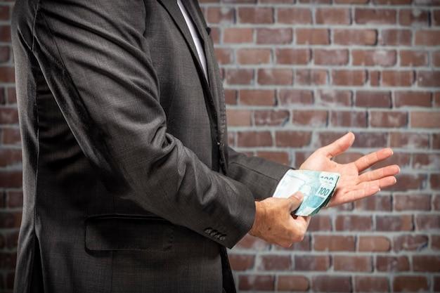 Homem de negócios segurando notas de dinheiro com uma algema na prisão. conceito de corrupção, políticos corruptos, negócios ilegais. fundo de tijolo.