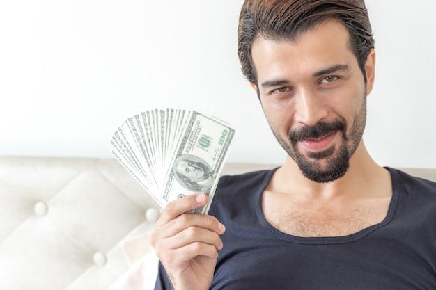 Homem de negócios segurando notas de dólar americano no escritório em casa