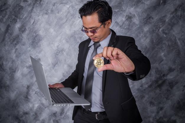 Homem de negócios, segurando o bitcoin dourado com computador portátil