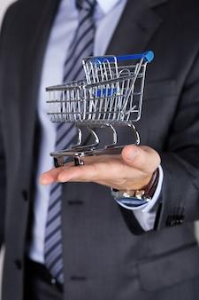 Homem de negócios segurando o carrinho de compras. conceito de oferta, compra ou venda de negócios