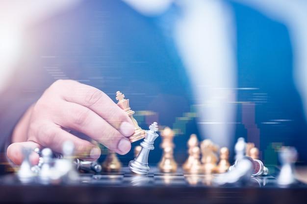 Homem de negócios segurando o rei dourado de xadrez para terminar o jogo