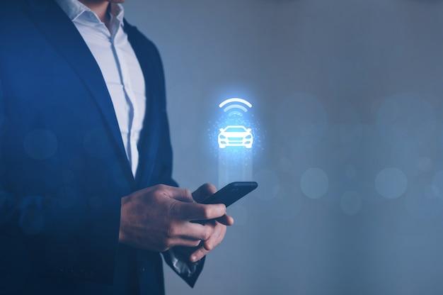 Homem de negócios, segurando o telefone com o ícone de carro inteligente. veículo inteligente
