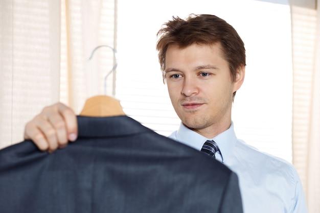 Homem de negócios segurando seu casaco e olhando para ele pronto para colocá-lo. preparando-se para algum evento ou novo dia de trabalho.