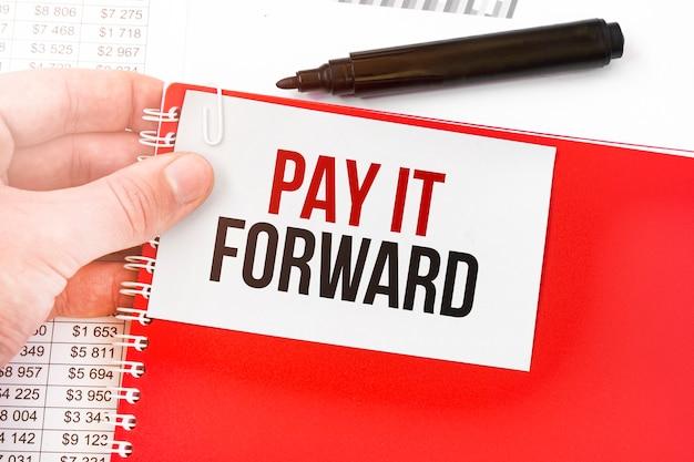 Homem de negócios segurando um caderno vermelho e um cartão branco com o texto pague adiante. conceito financeiro