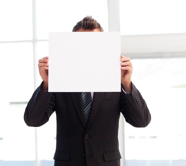 Homem de negócios segurando um cartão branco na frente de seu rosto