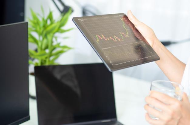 Homem de negócios segurando um dispositivo inteligente com gráfico de ações e negociação